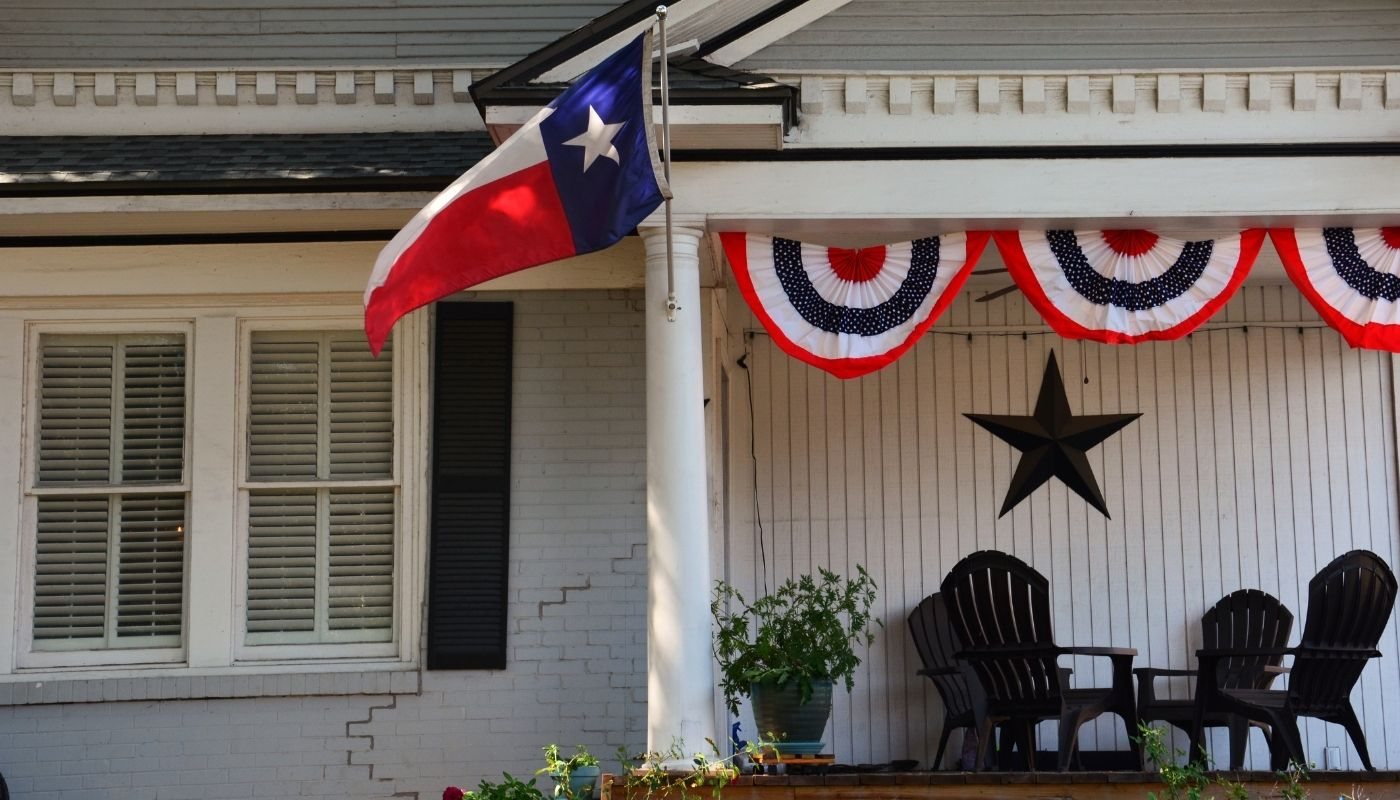 Front porch of home with Texas flags outside